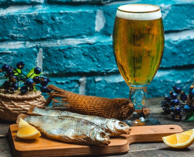 Peixe defumado servido com cerveja Foto gratuita