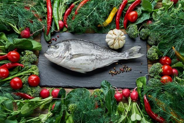 Peixe dorada e vegetais verdes ao redor na mesa de madeira velha. vista superior, comida saudável. Foto Premium