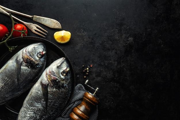 Peixe dorado com ingredientes no escuro Foto Premium