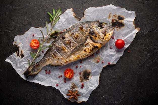 Peixe dourado fresco frito com especiarias em fundo preto Foto Premium
