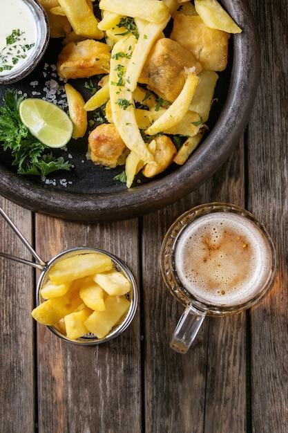 Peixe e batatas fritas com molho Foto Premium