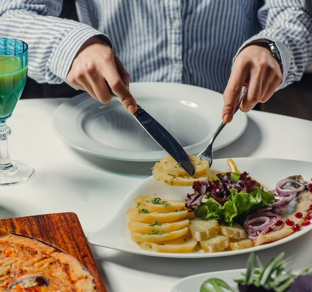 Peixe enlatado com fatias de batata cozida, picles de pepino, cebola roxa, alface, romã Foto gratuita