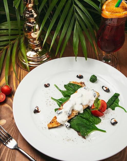 Peixe ensopado em molho cremoso, tomate, salsa no prato, faca, garfo mesa de madeira leve Foto gratuita