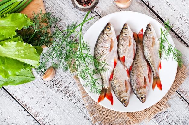 Peixe fresco com alecrim em um prato na mesa de madeira Foto Premium