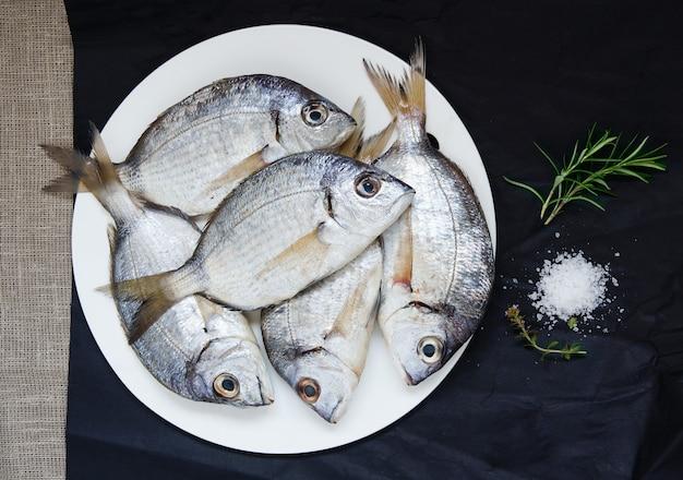 Peixe fresco cru misto para a preparação de sopa, dourada, escorpião, salmonete e groselha. vista do topo Foto Premium