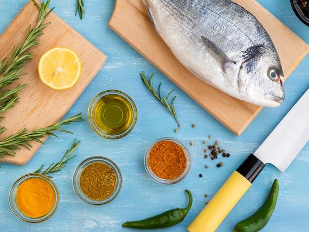 Peixe fresco em uma placa de madeira pronta para ser cozido Foto gratuita