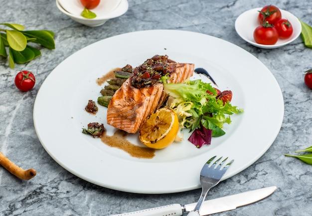Peixe frito com legumes em cima da mesa Foto gratuita
