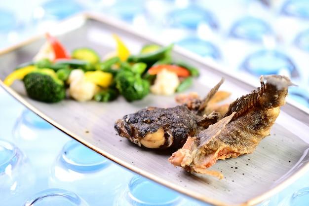 Peixe frito com legumes. goby do assado Foto Premium