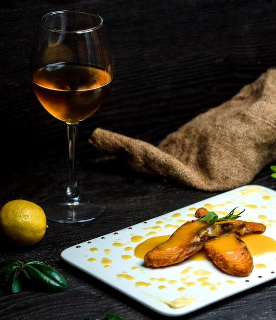 Peixe frito derramado com molho de limão e uma taça de champanhe Foto gratuita
