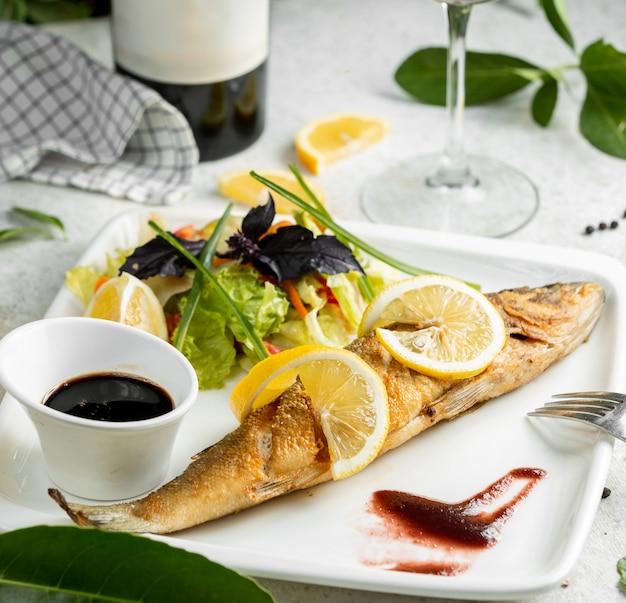 Peixe frito, guarnecido com rodelas de limão, servido com salada e nar sharab Foto gratuita