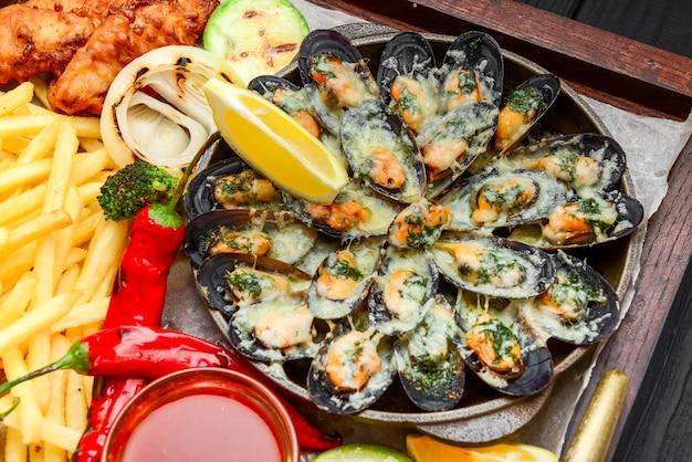 Peixe frito, mexilhões e camarão com batatas Foto Premium