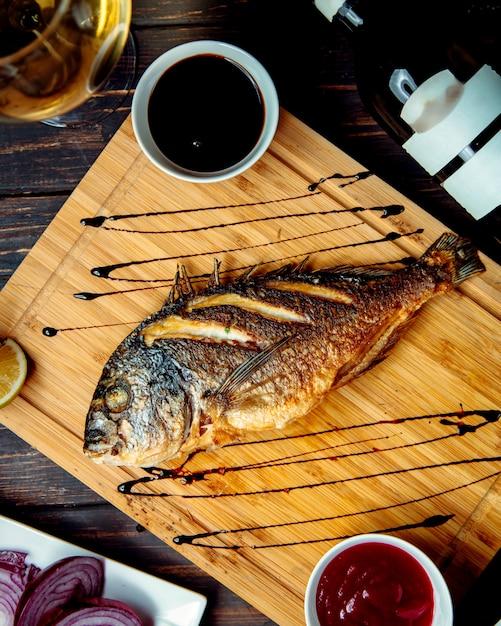 Peixe frito na mesa de madeira em cima da mesa Foto gratuita
