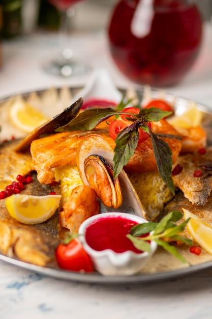 Peixe grelhado assado e frutos do mar servidos com ervas, limão e molho de tomate vermelho. Foto gratuita