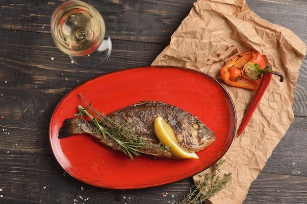 Peixe grelhado com limão e um raminho de alecrim. em um prato vermelho em uma mesa de madeira Foto Premium