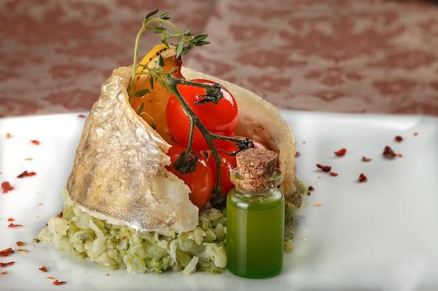 Peixes cozidos em um prato lateral vegetal com tomates de cereja. Foto Premium