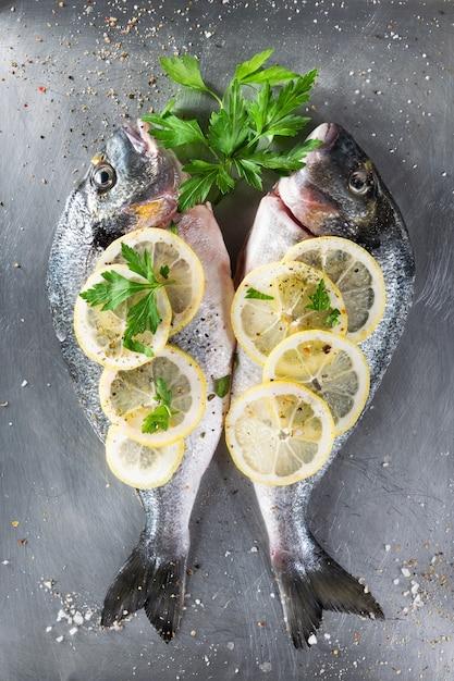 Peixes crus frescos do sargo decorados com fatias, ervas e salsa do limão no fundo claro. Foto Premium