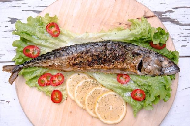 Peixes fritados com fatias do limão na salada verde da alface e na paprika vermelha. peixe inteiro assado de cavala servido na chapa de madeira com legumes Foto Premium