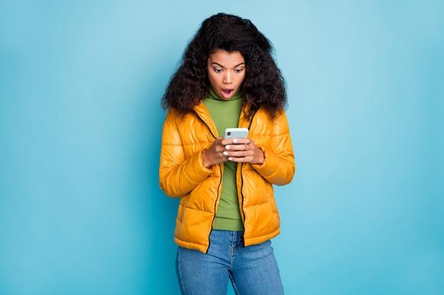 Pele escura senhora encaracolada boca aberta segurando telefone mãos não acreditar nos olhos comentários negativos usar casaco jeans suéter amarelo parede azul isolada Foto Premium
