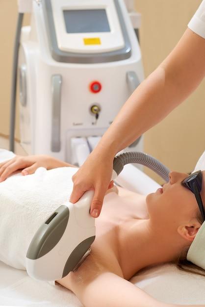 Pele lisa sob os braços. mulher fazendo depilação a laser Foto Premium
