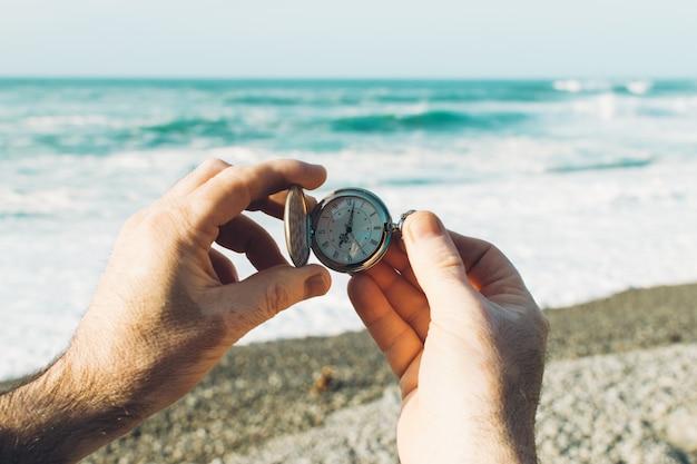 Pele vitiligo. mãos de homem segurando um relógio de bolso. fundo da praia. conceito de tempo. fim dos feriados Foto Premium
