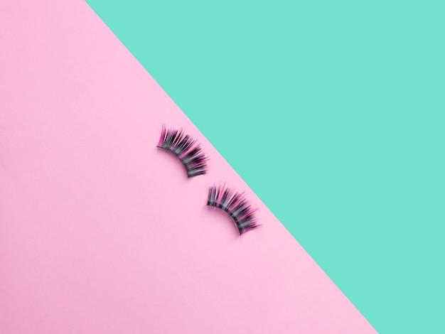 Pêlos longos cabelos coloridos. composição plana leiga com cílios postiços em fundo rosa e turquesa Foto Premium
