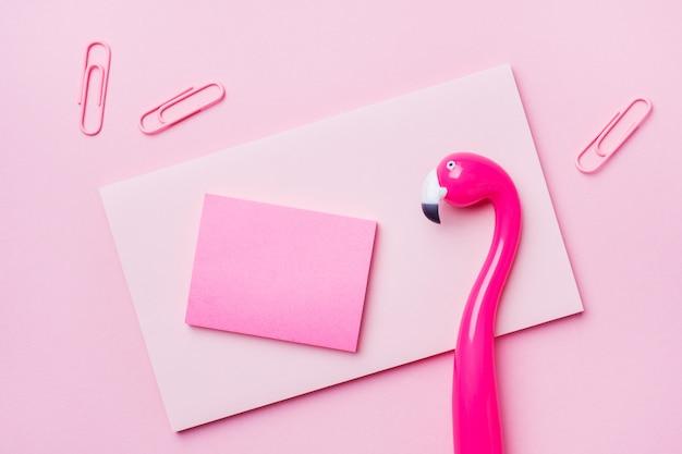 Pena do flamingo e almofada de escrita cor-de-rosa no rosa. lay plana. Foto Premium