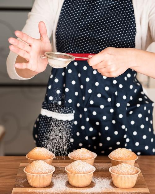 Peneirar açúcar em pó em muffins de mulher Foto gratuita