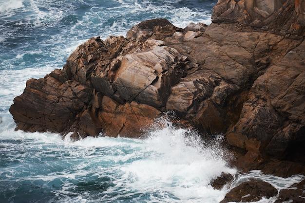 Penhasco rochoso perto de um corpo de água áspero com as ondas espirrando as rochas Foto gratuita