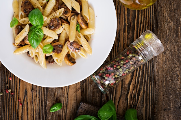 Penne de macarrão vegetal vegetariano com cogumelos em uma tigela branca na mesa de madeira. comida vegana. vista do topo Foto gratuita
