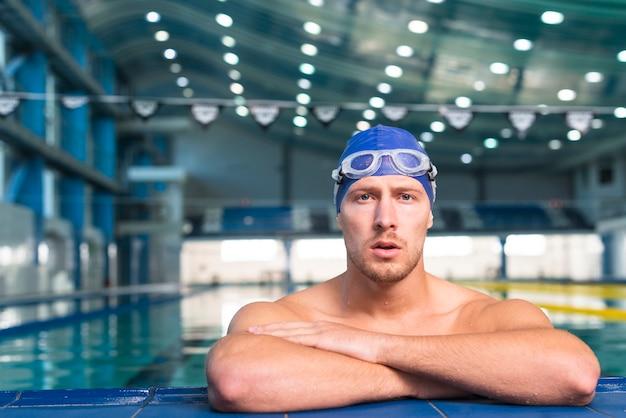 Pensador nadador masculino, olhando para o fotógrafo Foto gratuita