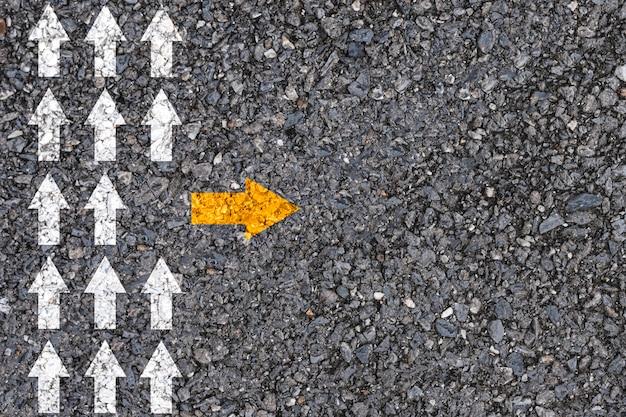 Pensamento diferente e conceito de interrupção de negócios e tecnologia. seta amarela fora da direção da linha com a seta branca no asfalto da estrada. Foto Premium
