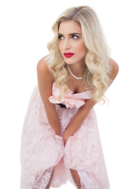 Pensando no modelo loiro no vestido rosa posando as mãos nas coxas Foto Premium