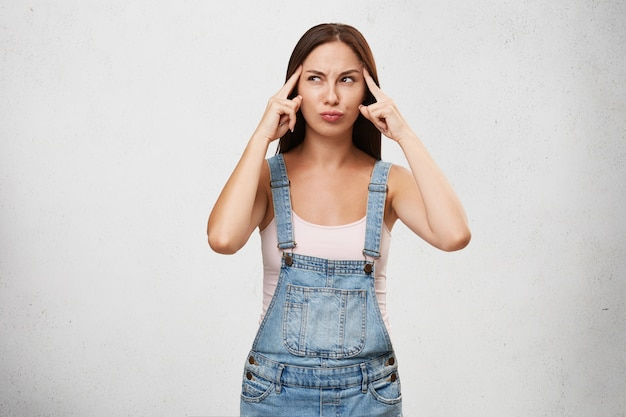 Pensativa fêmea concentrada de macacão jeans, mantendo os dedos nas têmporas, tentando ter uma ideia, olhando pensativamente para o lado, isolada sobre a parede branca em branco. jovem tentando lembrar resposta certa Foto gratuita