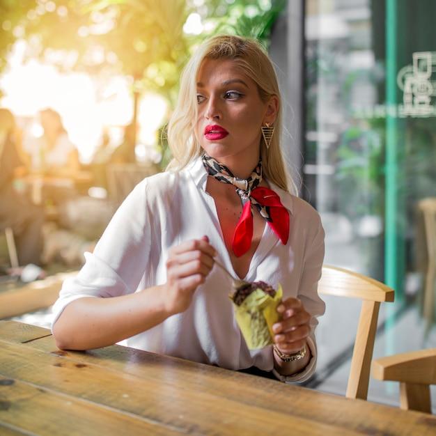 Pensativa jovem comendo muffins com colher no café Foto gratuita