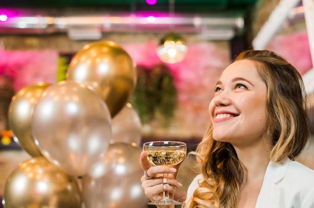 Pensativa jovem sorridente segurando o copo de uísque no bar Foto gratuita