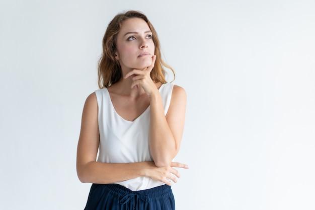 Pensativa mulher bonita tocando o queixo com os dedos Foto gratuita
