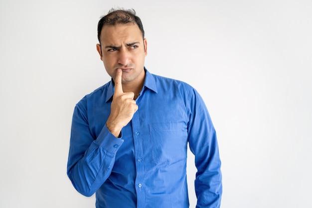 Pensativo homem indiano tocando os lábios e olhando para longe Foto gratuita