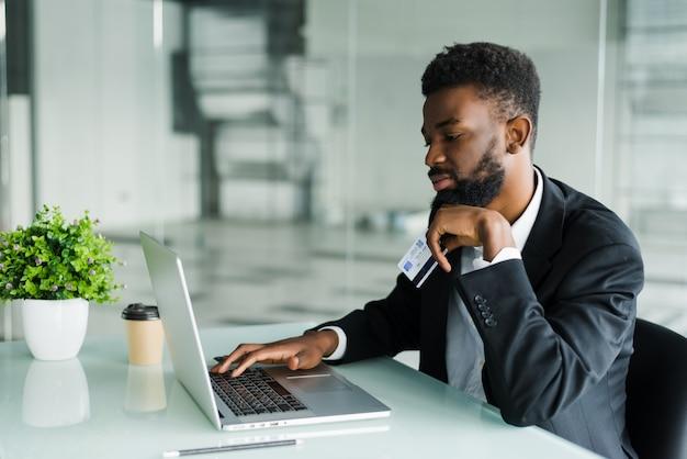 Pensativo jovem empresário americano africano trabalhando no laptop no escritório Foto gratuita