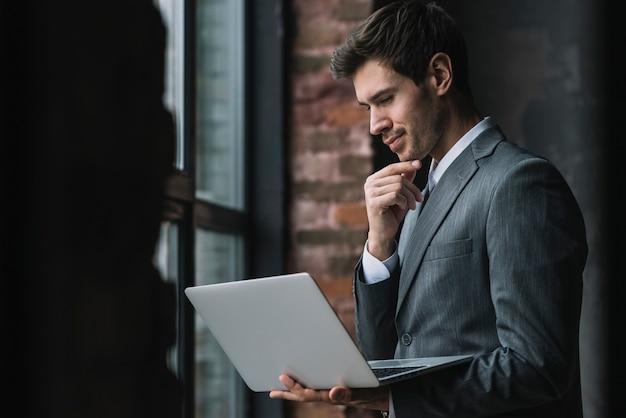 Pensativo jovem empresário inteligente olhando para laptop Foto gratuita