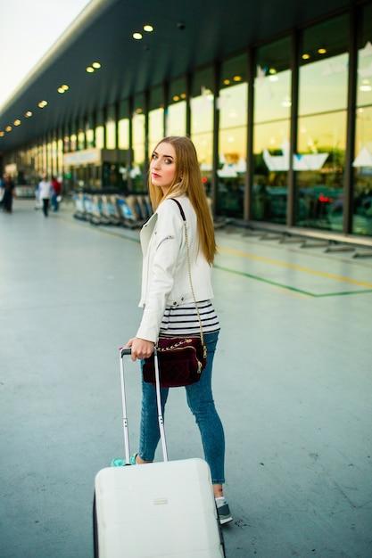 Pensativo, jovem, mulher, passeios, branca, mala, ao longo, aeroporto Foto gratuita