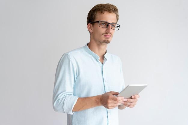 Pensativo jovem segurando o computador tablet Foto gratuita