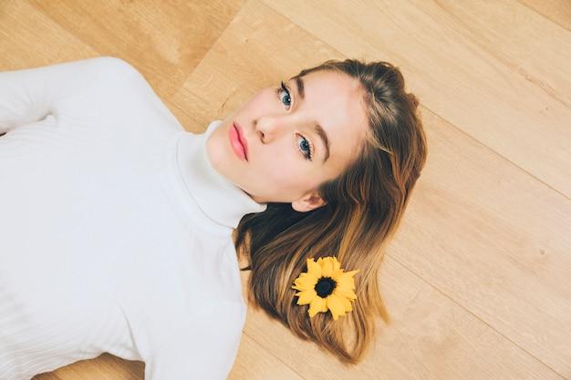 Pensativo, mulher, com, flor cabelo, mentindo chão Foto gratuita