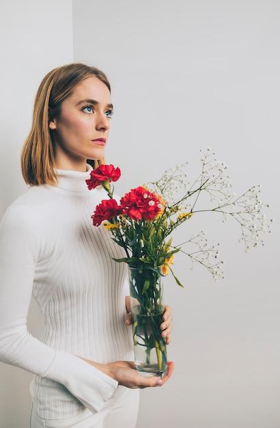 Pensativo, mulher, com, flores brilhantes, em, vaso, em, parede Foto gratuita