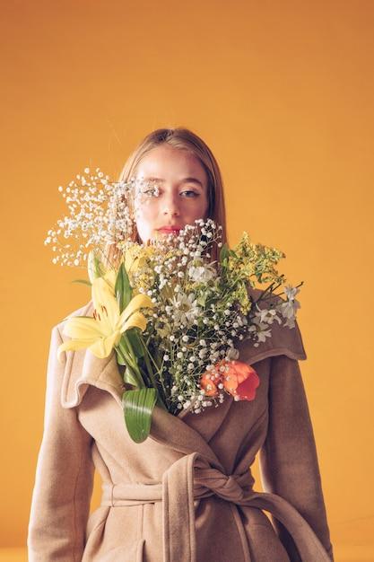 Pensativo, mulher, ficar, com, buquê flores, em, agasalho Foto gratuita