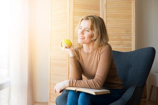 Pensativo, mulher senta-se com livro, e, maçã Foto gratuita