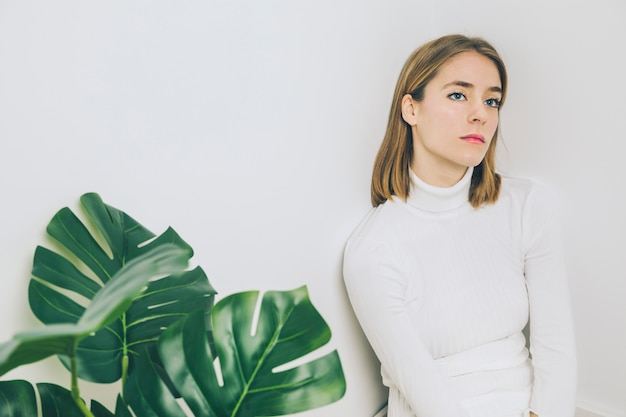 Pensativo, mulher senta-se, perto, planta verde Foto gratuita