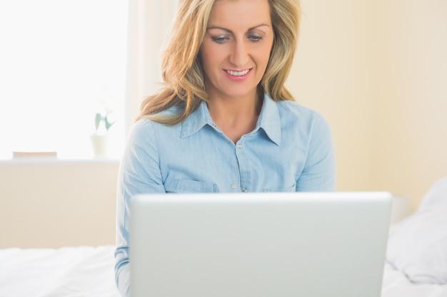 Pensativo, mulher, sentando, ligado, um, cama, usando, dela, laptop Foto Premium
