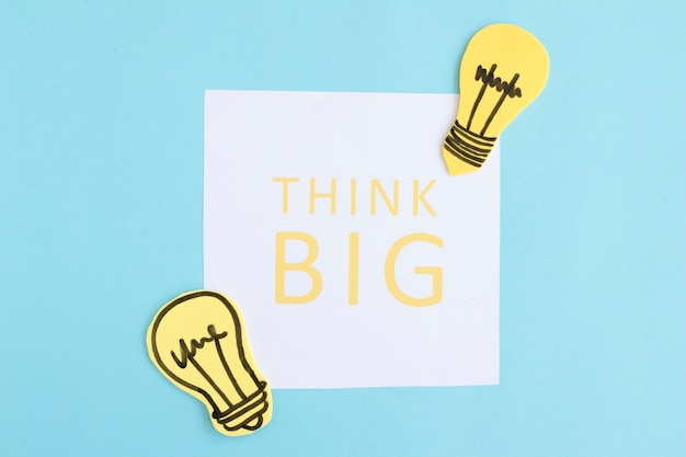 Pense grande texto em papel branco com lâmpadas em fundo azul Foto gratuita