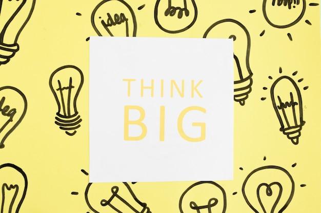 Pense grande texto na mão desenhada lâmpada sobre o fundo amarelo Foto gratuita
