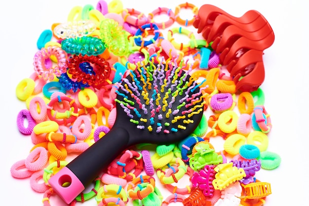 Pente colorido brilhante em elásticos coloridos para o cabelo em um fundo branco. Foto Premium